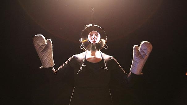 La soupe aux caillloux par Pan ! la compagnie. Une femme portant un tablier noir, aux mains des maniques argentées fait la moue au travers d'une passoire qui semble léviter.